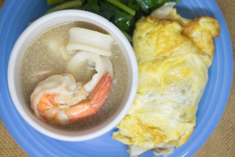 Gebraden noedel in ei met pijlinktvis, garnalen en boerenkool in jus stock foto's