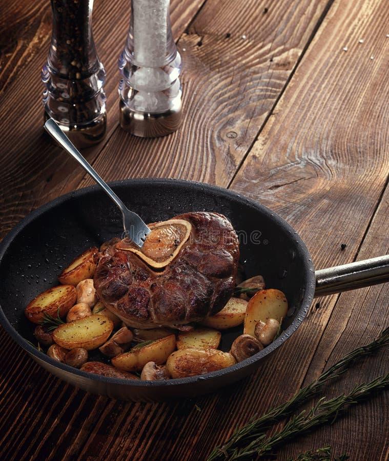 Gebraden ossobuco met plantaardige ragoût van aardappels en paddestoelen stock fotografie
