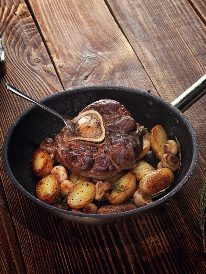 Gebraden ossobuco met plantaardige ragoût van aardappels en paddestoelen stock foto