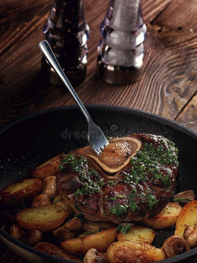 Gebraden ossobuco met plantaardige ragoût van aardappels en paddestoelen royalty-vrije stock afbeeldingen