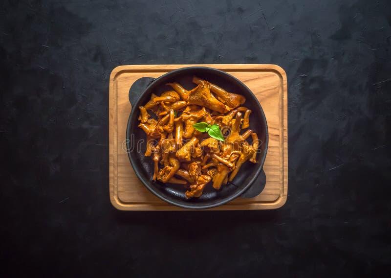 Gebraden paddestoelencantharellen in een pan op een zwarte lijst stock foto