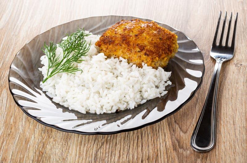 Gebraden pasteitje met rijst, dille in bruine plaat, vork op houten lijst stock afbeelding