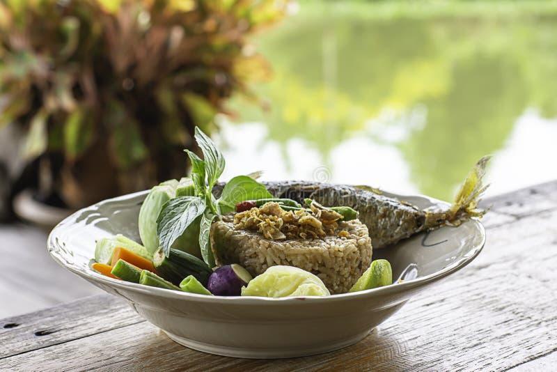 Gebraden rijst met Spaanse peper kruidig met vissen en groenten in witte plaat op houten lijst Achtergrondrivieren en bomen stock fotografie