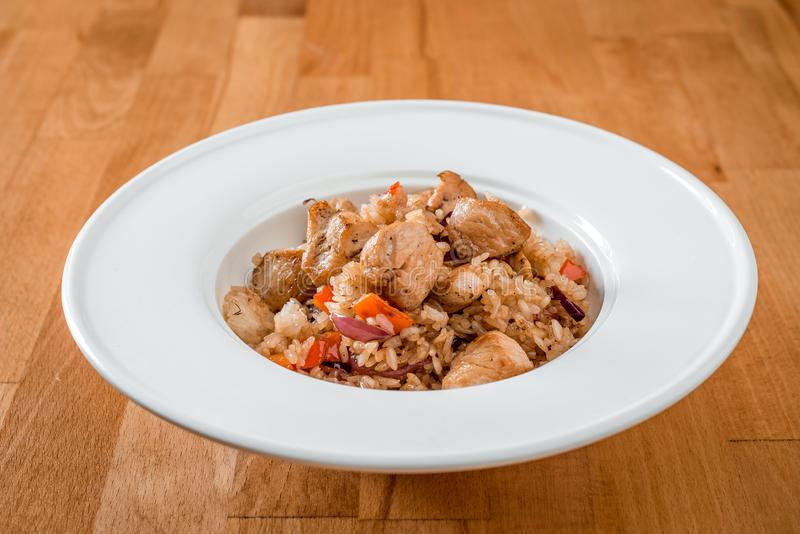 Gebraden rijst met vlees en groenten in een witte plaat Close-up stock fotografie