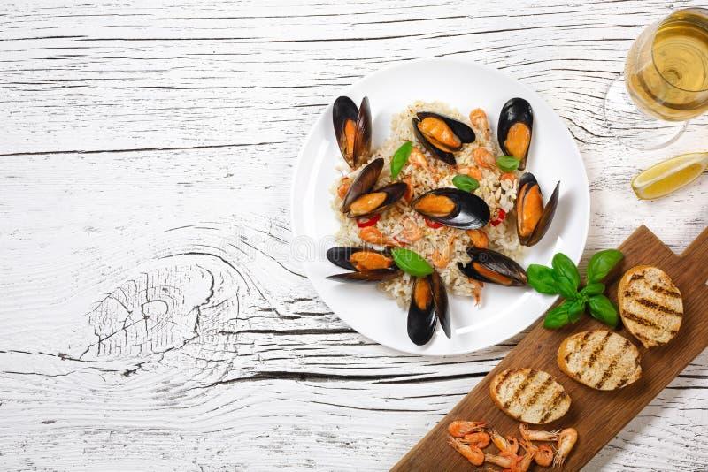 Gebraden rijst met zeevruchtenmosselen, garnalen en basilicum in een plaat met wijnglas en geroosterde baguette op witte gebarste royalty-vrije stock fotografie