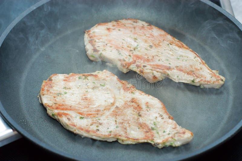 Gebraden schnitzel op een teflonpan stock fotografie