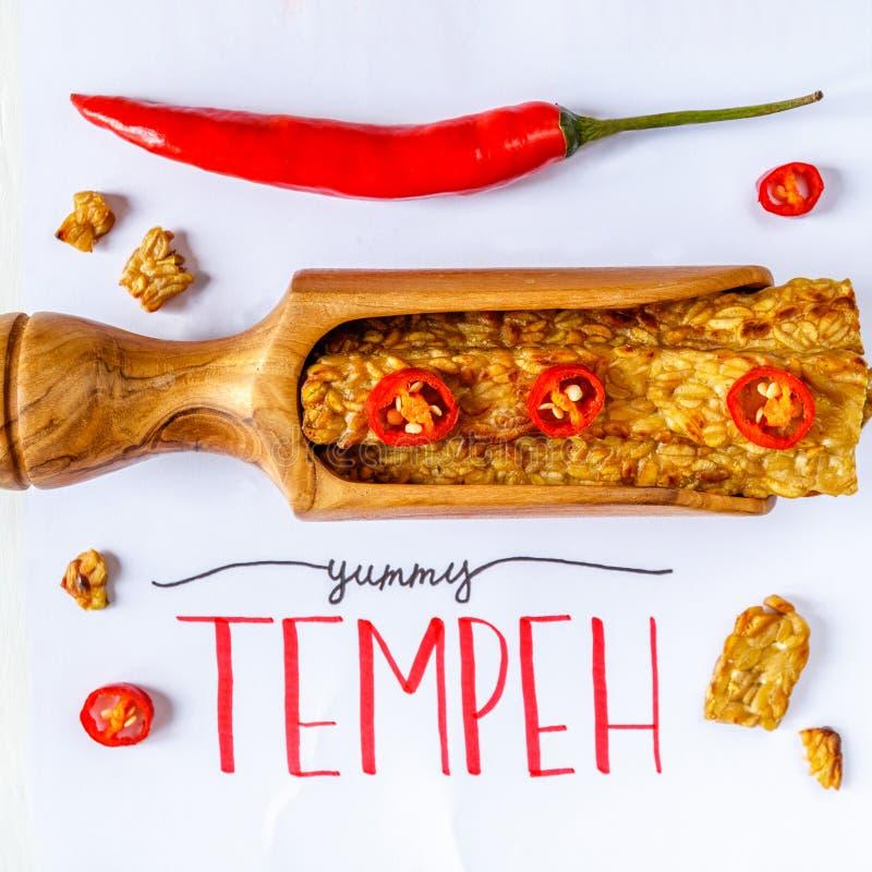 Gebraden tempeh in een houten die lepel met koel wordt verfraaid YUMMY TEMPEH-titel Hoogste mening royalty-vrije stock afbeeldingen