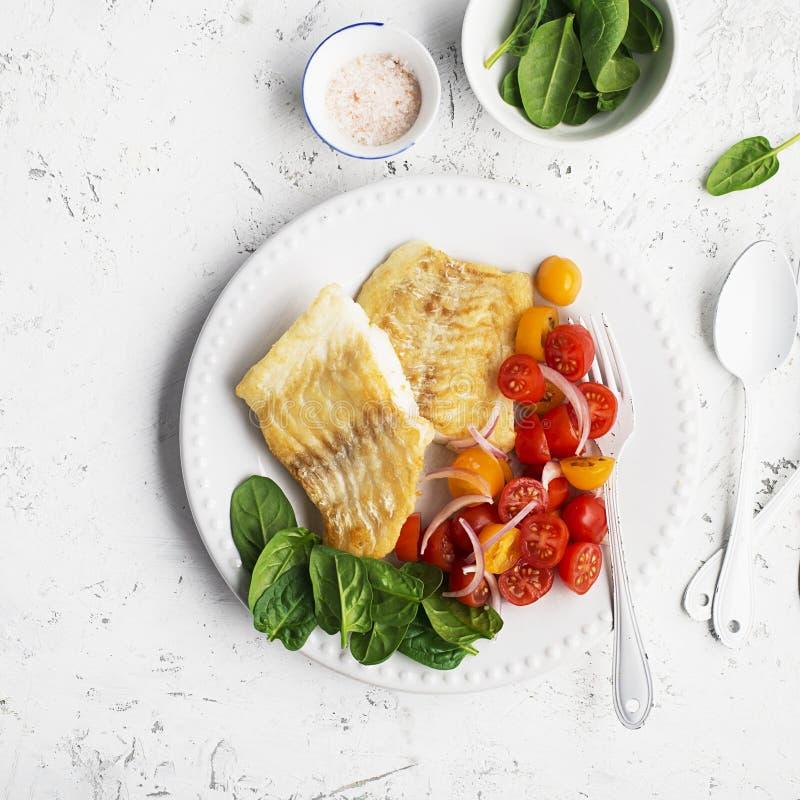 Gebraden verse overzeese witte kabeljauwfilet met salade van kersentomaten en zoete rode uien Het concept van het voedsel Hoogste royalty-vrije stock afbeelding