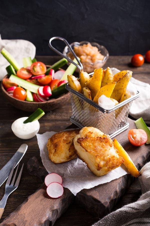 Gebraden visfilet met aardappelen in de schil stock afbeeldingen
