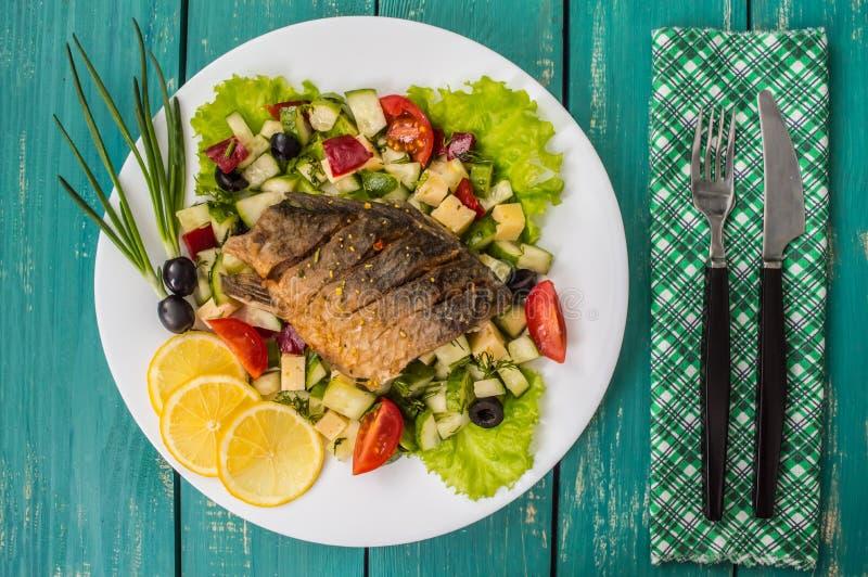 Gebraden visfilet op een bed van Caesar-salade Houten achtergrond Hoogste mening royalty-vrije stock foto's