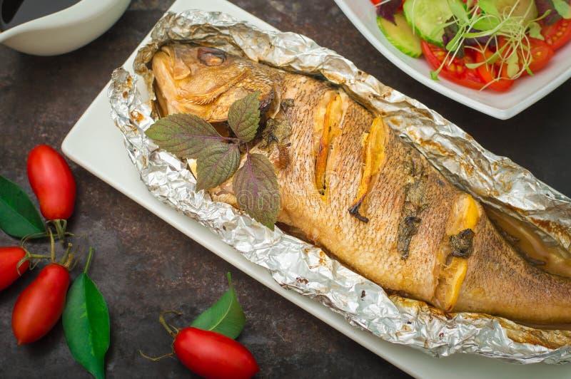 Gebraden vissen met verse tomaten, kruiden en citroen Oude zwarte achtergrond Hoogste mening royalty-vrije stock foto