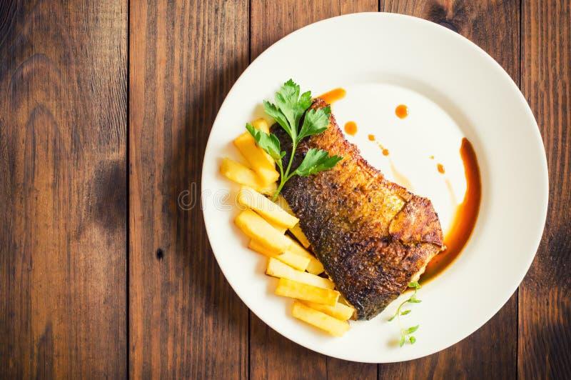 Gebraden vissenlapje vlees met gebraden gerechten Houten achtergrond Hoogste mening Close-up stock afbeeldingen