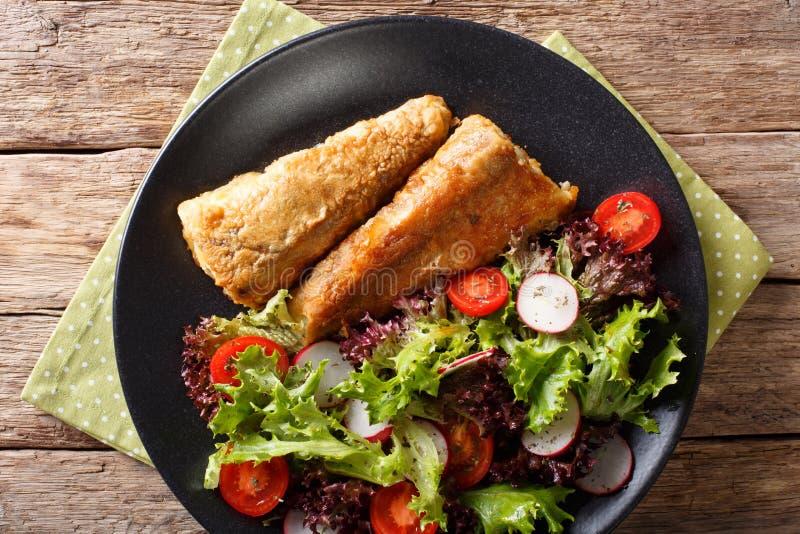 Gebraden vissenstokvissen met dicht salade van tomaat, radijs en sla royalty-vrije stock foto