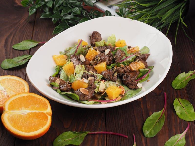 Gebraden vlees met oranje saus op een witte plaat stock afbeelding