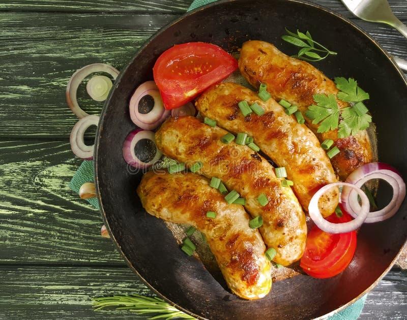 Gebraden worst op een pan, tomaat, ui, barbecueplattelander op een zwarte oude houten achtergrond stock foto's
