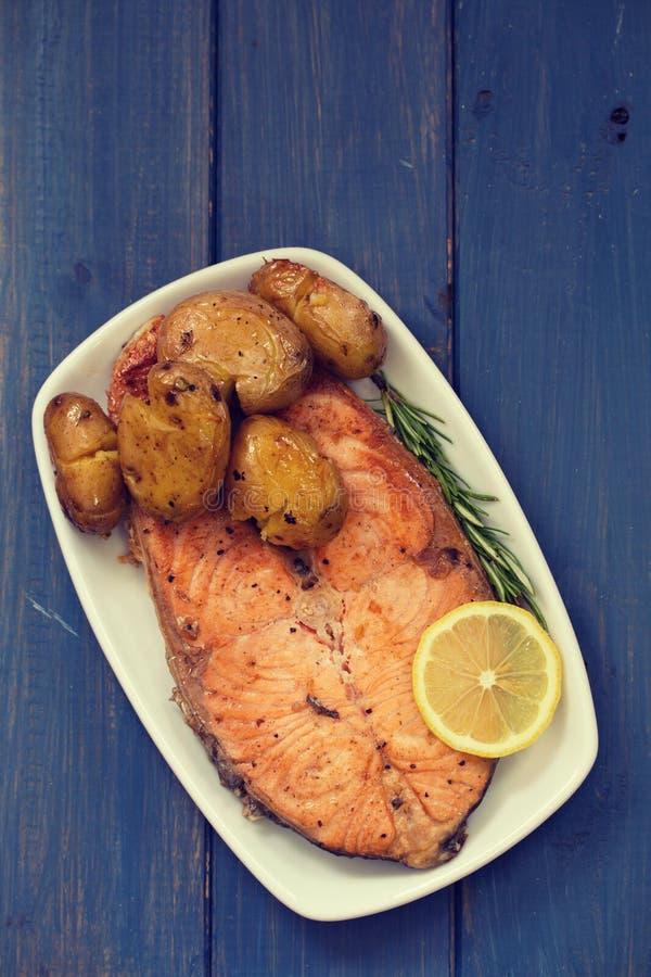 Gebraden zalm met aardappel en citroen op schotel op blauwe achtergrond stock afbeeldingen