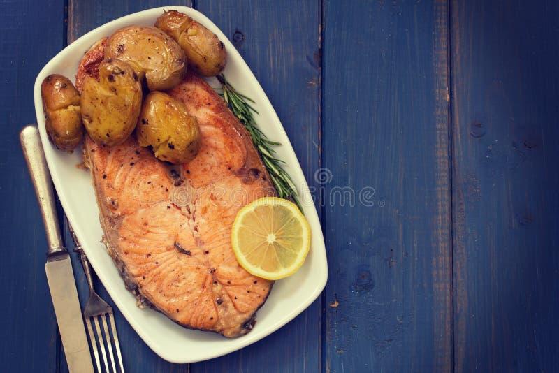 Gebraden zalm met aardappel op schotel op blauwe achtergrond stock foto's