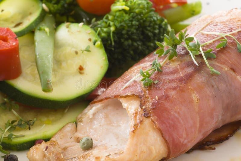 Gebraden zalm met ham en groenten stock foto's