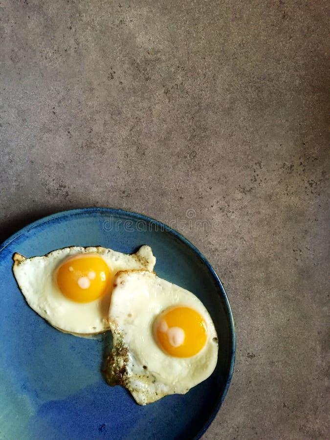 Gebraden zonnig-kant op eieren geschoten top down op blauwe plaat stock foto's