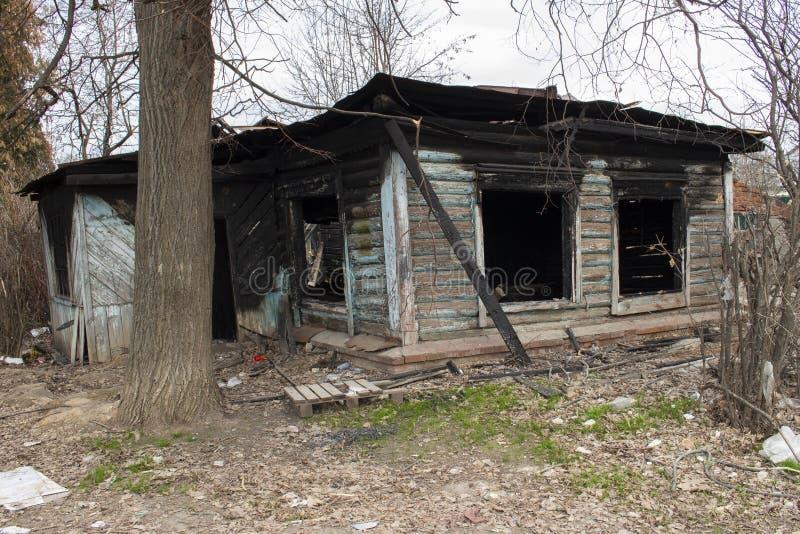 Gebrand houten buitenhuis De woonplaats van het land na een brand Zwarte verkoolde venstermuren royalty-vrije stock fotografie