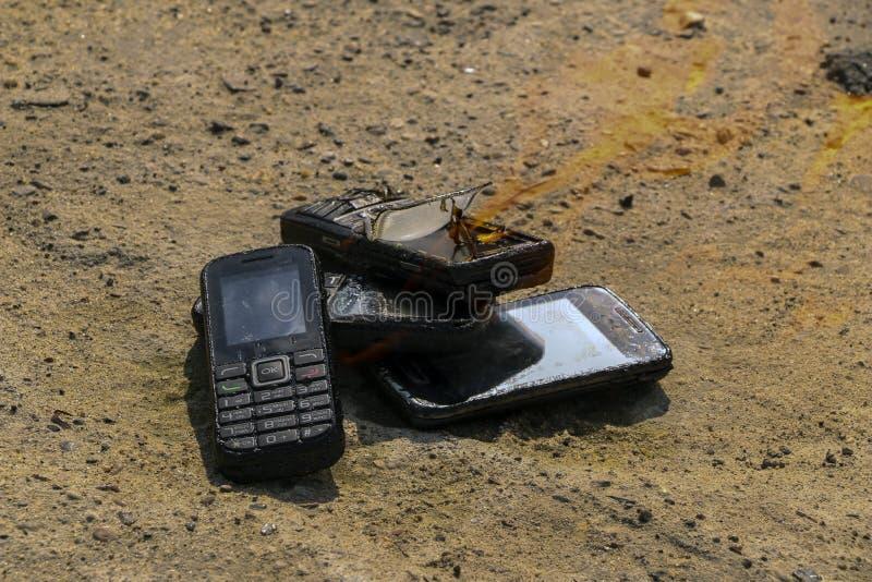 Gebrannte Handys auf strukturellem konkretem Hintergrund Konzept: Gefahr der Anwendung von minderwertigen Handys lizenzfreies stockfoto
