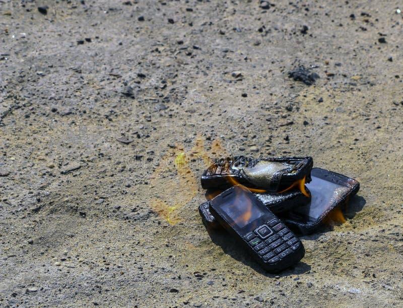 Gebrannte Handys auf strukturellem konkretem Hintergrund Konzept: Gefahr der Anwendung von minderwertigen Handys stockbilder