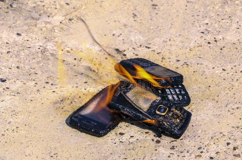 Gebrannte Handys auf strukturellem konkretem Hintergrund Konzept: Gefahr der Anwendung von minderwertigen Handys lizenzfreie stockbilder