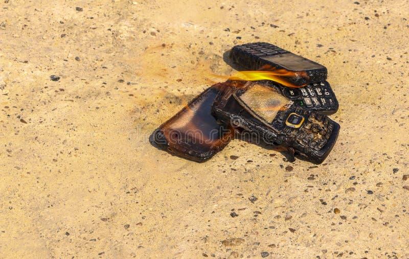 Gebrannte Handys auf strukturellem konkretem Hintergrund Konzept: Gefahr der Anwendung von minderwertigen Handys stockfotografie