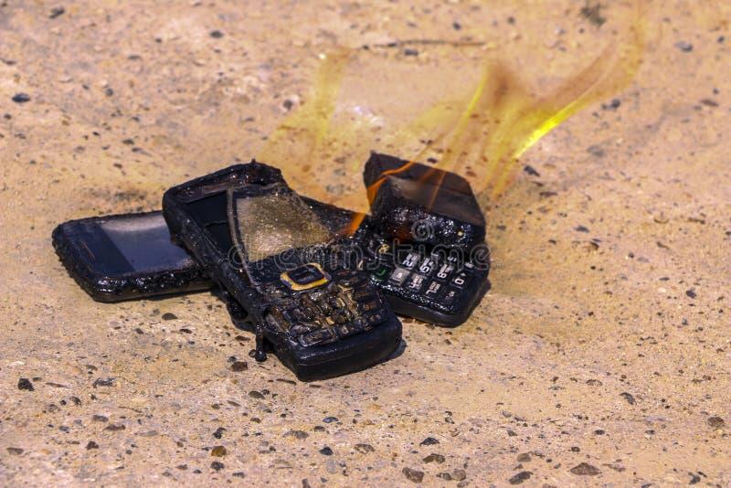 Gebrannte Handys auf strukturellem konkretem Hintergrund Konzept: Gefahr der Anwendung von minderwertigen Handys lizenzfreies stockbild