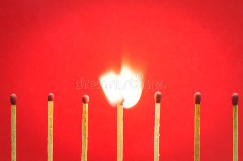 Gebrannte Matcheinstellung auf rotem Hintergrund für Ideen und Inspiration lizenzfreies stockfoto