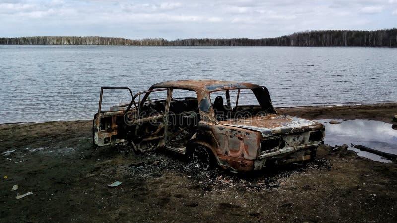 Gebranntes Auto auf einer Seeküste stockbilder