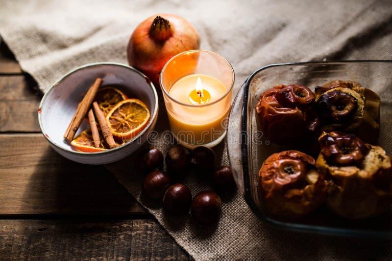 Gebratene Äpfel in einem Glasbehälter mit Kastanien, Zimt, Orange und Granatapfel stockbild