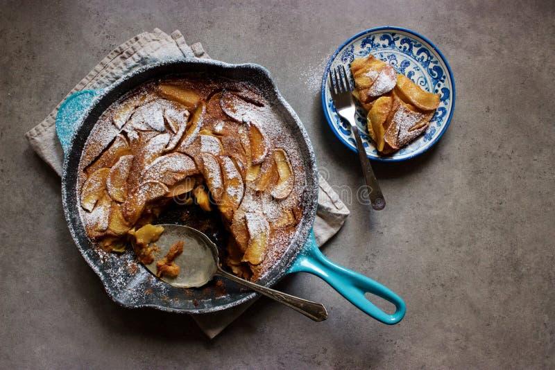Gebratene Apfel Clafoutis (französischer Vanillepuddingkuchen) in geworfenem Eisenstein stockfotos