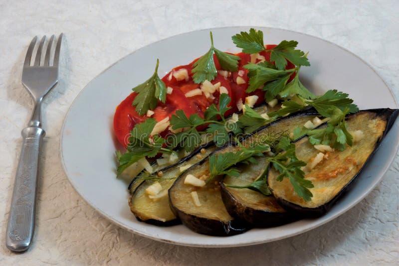 Gebratene Aubergine mit Tomaten, Knoblauch und Kraut-, geschmackvollem und gesundemlebensmittel stockfotografie