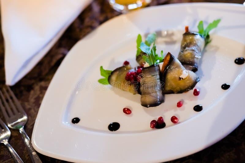 Gebratene Aubergine rollt mit der Walnusspaste, die mit Koriander- und Granatapfelsamen verziert wird Salat der gebratenen Auberg lizenzfreie stockfotos