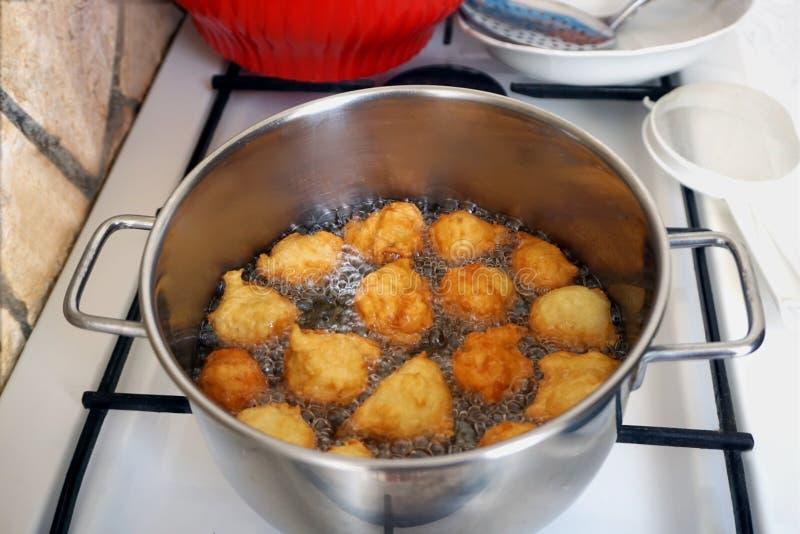 Gebratene Bälle werden im Öl auf dem Ofen gebraten Zubereitung eines selbst gemachten Nachtischs auf der traditionellen Weise lizenzfreies stockbild