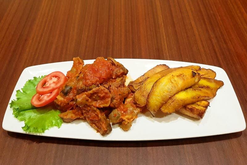 Gebratene Bananen und Muskelmageneintopfgericht mit frischen Tomaten - nigerische Nahrung - Zartheit stockfotografie