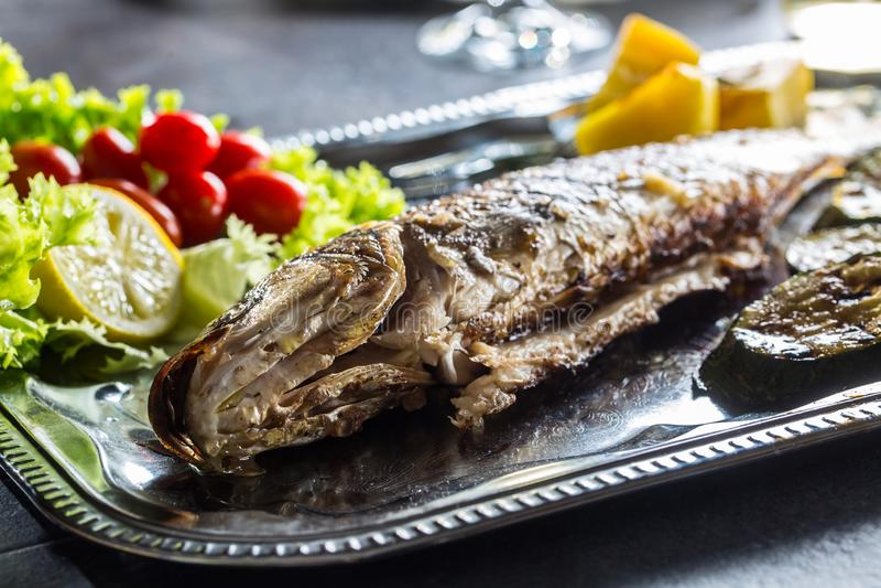 Gebratene Fische auf Teller mit frischem und gegrilltem Gemüse lizenzfreie stockfotos