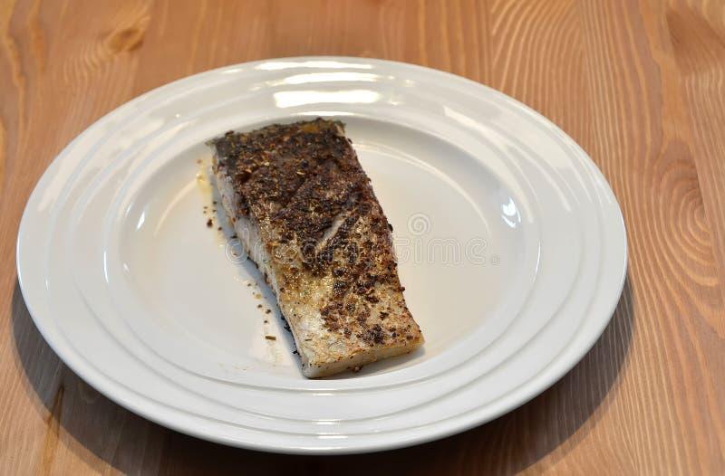 Gebratene Fische essen mit Gewürz auf weißem Plattenfoto zu Mittag lizenzfreie stockbilder