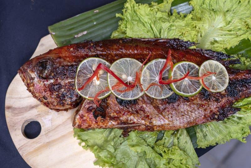 Gebratene Fische mit frischem gr?nem Salat und Zitrone von Bali, Indonesien, Nahaufnahme K?stlicher gebratener Seefisch mit Zitro lizenzfreies stockfoto