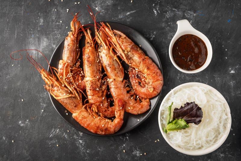 Gebratene gegrillte Garnelen mit Reisnudel, Soße und Kopfsalat, dunkler Hintergrund stockbilder