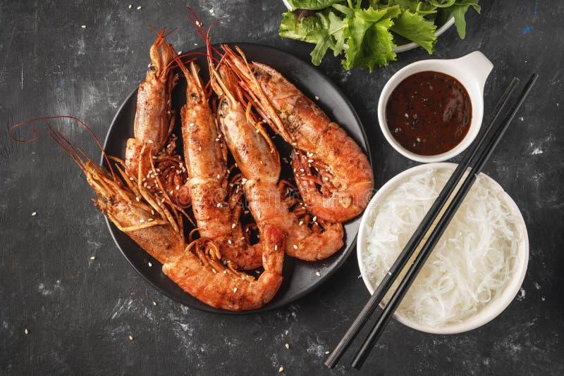 Gebratene gegrillte Garnelen mit Reisnudel, Soße und Kopfsalat, dunkler Hintergrund lizenzfreie stockfotos