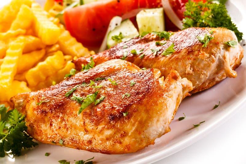 Gebratene Hühnerbrustpommes-frites und Gemüsesalat lizenzfreie stockbilder