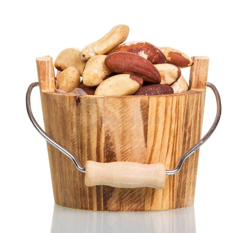 Gebratene Körner von Erdnüssen in einem hölzernen Eimer lokalisiert auf Weiß lizenzfreies stockfoto
