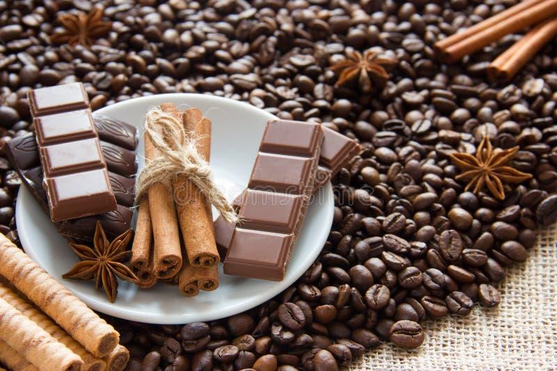 Gebratene Kaffeebohnen mit einem Bündel Zimtstangen mit Milch und schwarze Schokolade und Kekse auf dem Rausschmiß stockbilder