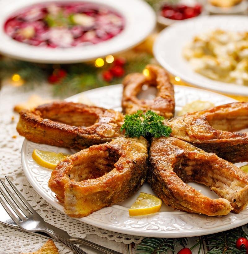 Gebratene Karpfenfischscheiben auf einer weißen Platte, Abschluss oben Traditioneller Weihnachtsabendsteller stockfotos