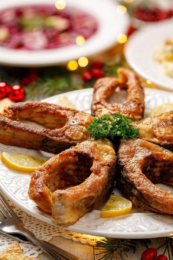 Gebratene Karpfenfischscheiben auf einer weißen Platte, Abschluss oben Traditioneller Weihnachtsabendsteller lizenzfreie stockfotos
