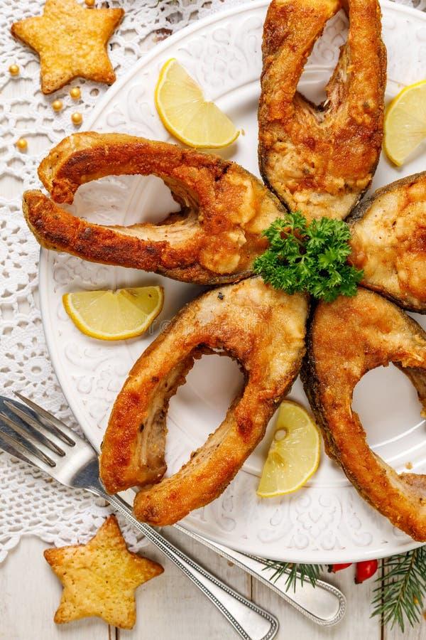 Gebratene Karpfenfischscheiben auf einer weißen Platte, Draufsicht Traditioneller Weihnachtsabendsteller lizenzfreie stockbilder