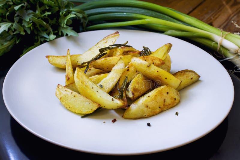 Gebratene Kartoffelkeile mit Kräutern und Salz stockbild