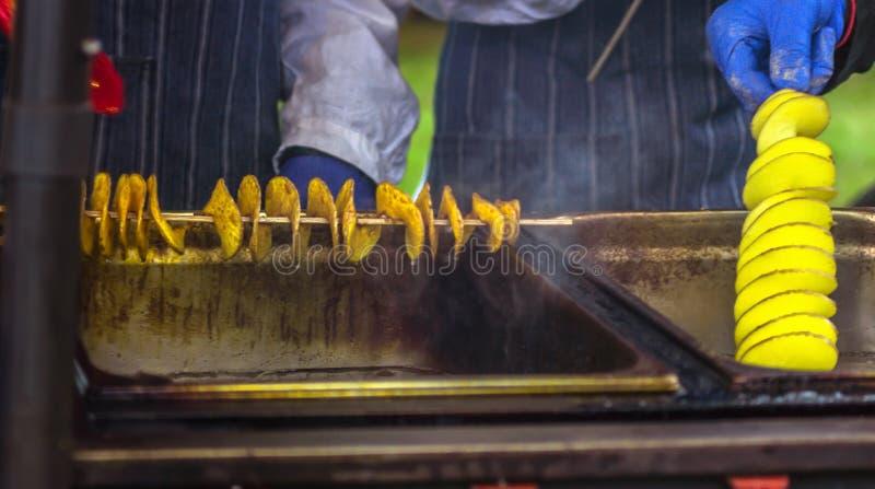 Gebratene Kartoffeln in Form von Spirale auf hölzernem Stock Kartoffeln gebraten bis goldene Farblügen auf Metallbehälter während lizenzfreie stockbilder